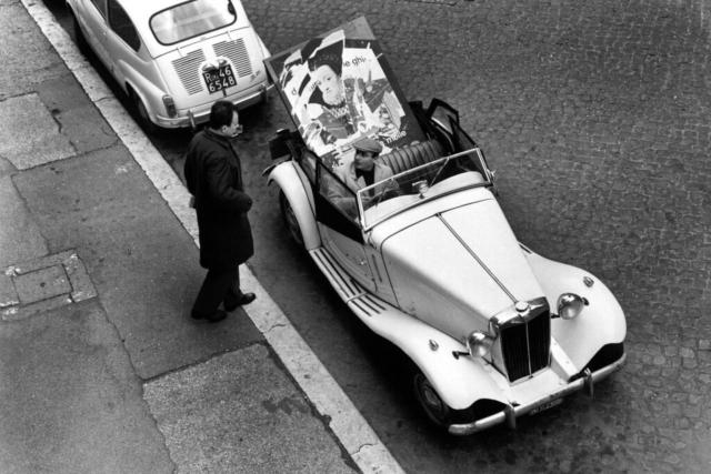 Mimmo Rotella (1918-2006) L'artista con l'opera alla guida della sua macchina MG Roma, 1959